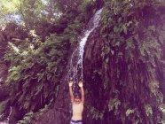 Garçon debout sous une cascade en été — Photo de stock