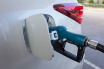 Close-up of gas nozzle in fuel tank of a car — Stock Photo