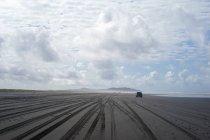 Malerischer Blick auf das Autofahren an einem leeren Sandstrand — Stockfoto