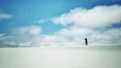 Silhouette der Mann, der in der Wüste gegen blau mit weißen Wolken sly — Stockfoto