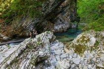 Uomo che scatta foto con macchina fotografica sulla roccia in natura, Vintgar Gorge, Slovenia — Foto stock