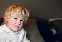 Sorridente ragazzo biondo indossa camicia bianca guardando la fotocamera — Foto stock