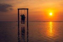 Силуэт поцелуев мужчины и женщины, стоящих на качелях в море на закате — стоковое фото