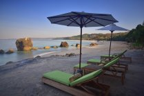 Sun loungers and parasols on beach in morning, West Sumba, Indonesia — Stock Photo