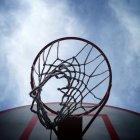 Низким углом зрения баскетбольное кольцо под пасмурным небом — стоковое фото