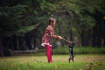 Ragazza che gioca con cane cucciolo nel parco — Foto stock