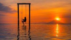 Силуэт женщины, сидящей на качелях в море на закате, Индонезия — стоковое фото