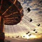 Carrusel vintage vacío balanceándose durante la puesta del sol - foto de stock