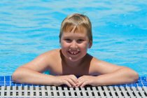 Portrait of smiling boy leaning on edge of swimming pool — Stock Photo