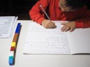 Ragazzo che fa i compiti di matematica alla scrivania — Foto stock