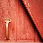 Metal handle on red wooden door, closeup view — Stock Photo