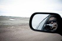 Frau mit Foto-Kamera im Außenspiegel des Autos — Stockfoto