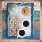 Vista superior da bandeja com café, açúcar e biscoitos na mesa de madeira — Fotografia de Stock