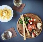 Вид зверху шинка, сир, parmigiana закусок та помідорів чері із сиром моцарелла — стокове фото