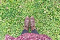 Baixa seção de mulher vestindo botas marrons em pé na grama — Fotografia de Stock