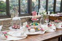 Mesa de madeira com doces festivos deliciosos, chá e café — Fotografia de Stock