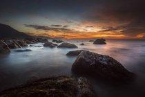 Vista panorámica de la puesta de sol sobre la costa rocosa - foto de stock