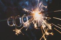 Los anillos de boda cuelgan de un bengala mientras se quema iluminando los anillos - foto de stock