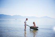 Ragazzo che spinge la sorella in carriola in mare — Foto stock