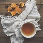 Té y naranjas secas en toalla sobre mesa de madera - foto de stock