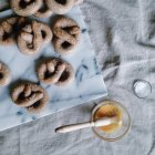 Homemade pretzels on white marble and bowl with egg yolk — Stock Photo
