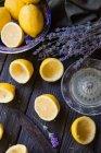 Citrons coupés en deux et ensemble avec des fleurs de lavande sur table en bois — Photo de stock