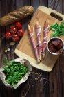 Bâtonnets de pain enveloppé dans du jambon de Parme avec tomates, roquette et pain — Photo de stock