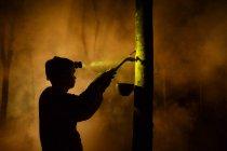 Людина з факелом tapping каучукового дерева в нічний — стокове фото