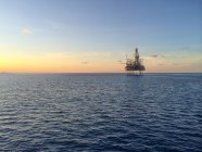 Scenic view of oil rig at beautiful sunset — Stock Photo