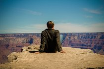 Rear view of a young man sitting on ledge of grand canyon and looking at view, arizona, USA — Stock Photo