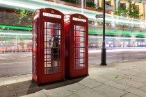 Vista panorámica de senderos de luz en el centro de Londres y cabinas telefónicas, Reino Unido - foto de stock