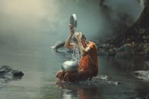 Novice monk cooling off in a creek, Asia — Stock Photo