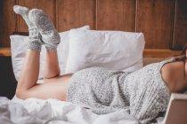 Image recadrée de femme attrayante avec une belle peau dans le pull et les chaussettes couchées sur le lit — Photo de stock