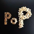 Palabra Pop escrito con palomitas de maíz sobre mesa negra - foto de stock