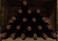 Stack di bottiglie di vino rosso sullo scaffale — Foto stock