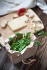 Свежая руккола в бумажной обертке с сыром над деревянным столом — стоковое фото
