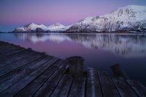 Заснеженные горы видны с деревянной пристани — стоковое фото
