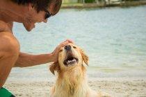 Крупным планом портрет человека поглаживая Золотой ретривер собака на пляже — стоковое фото