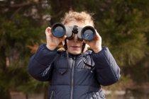 Garçon à la recherche par le biais de plein air jumelles — Photo de stock