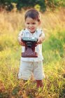 Smiling boy holding a vintage camera on grass — Stock Photo