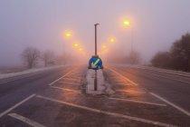 Freezing fog road in morning and turn sign, Cambridgeshire, England, UK — Stockfoto