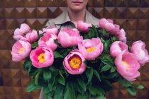 Primo piano donna che tiene il mazzo di bei fiori rosa — Foto stock