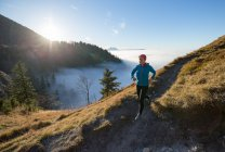 Woman Trail Running in the Mountains above the Clouds, Salzburg, Austria — Stock Photo