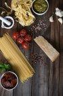 Pasta, pesto, garlic, tomatoes and parmesan on table — Stock Photo