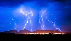 Huelga de iluminación sobre la estación de generación nuclear de Palo Verde detrás de la montaña Saddleback, Arizona, EE.UU. - foto de stock