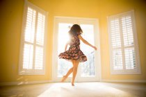 Молодая женщина танцует в солнечной комнате — стоковое фото