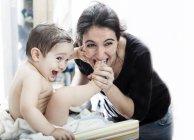 Entzückender kleiner Junge spielt mit glücklicher Mutter — Stockfoto