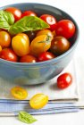 Bowl of cherry tomatoes with basil, closeup — Stock Photo
