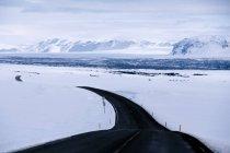Strada tortuosa attraverso neve coperto paesaggio invernale, Islanda — Foto stock