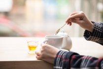 Обрезанное изображение женщины, положить мед в чашку чая — стоковое фото